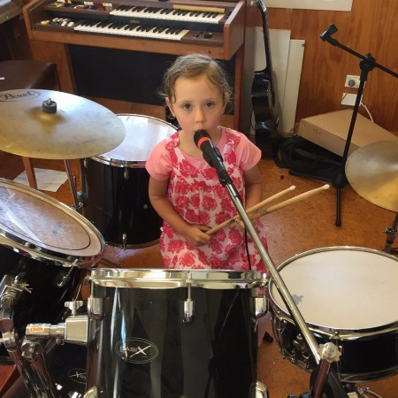 Little Girl in pink dress playing drums and singing